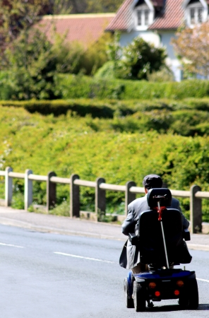 Rear view or senior man riding mobility scooter on countryside road.