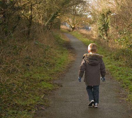 young boy in a winter coat walking away down a path