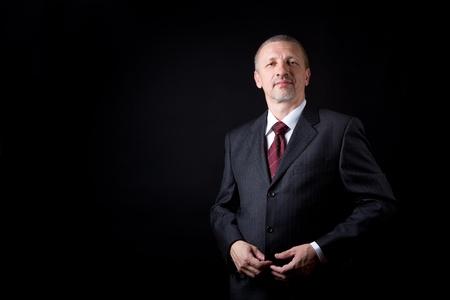 Photo pour Unshaven mature businessman with hand on his suit - image libre de droit