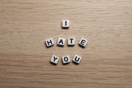 Photo pour Word I HATE YOU in white cubes on light wooden background for your design templates. - image libre de droit