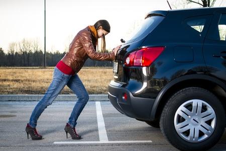 Young woman pushing broken car