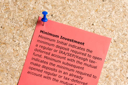 minimum investment word typed on a paper and pinned to a cork notice board