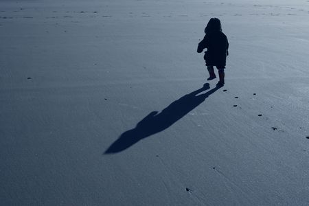 Boy walking on beach with determination