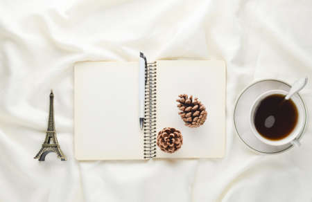Foto de Morning inspiration, cup of tea, notebook with a pen, pine cone, souvenir on a white bed sheet. Breakfast on the bed. The concept of dreams and the desire to travel. Top view. - Imagen libre de derechos