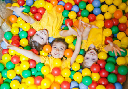 Photo for Three happy little kids girls in ball pit smiling happily at camera while having fun in children play center. Top view - Royalty Free Image
