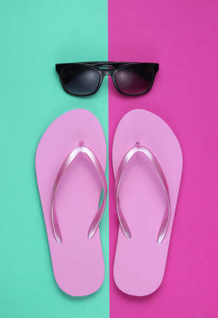 Photo pour Summer still life. Beach accessories. Fashionable beach pink flip flops, sunglasses on pink blue  paper background. Flat lay. Top view - image libre de droit