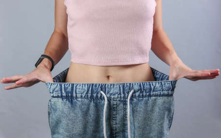 Photo pour The concept of losing weight. Woman in very big jeans on gray studio background. Crop photo - image libre de droit