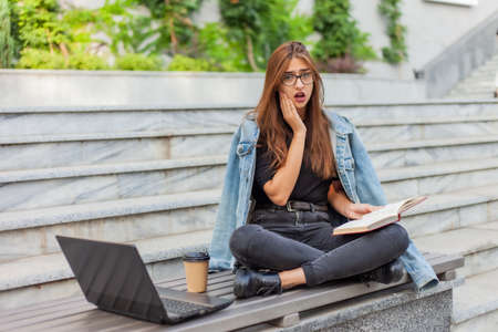 Photo for Modern students. Distance learning. Young enthusiastic woman reads book while sitting on bench with a laptop - Royalty Free Image