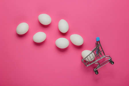 Photo pour Cart for shopping and chicken eggs on pink background. Minimalism food concept. Top view - image libre de droit