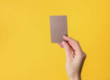 Photo for Female hand holds a blank brown business card on yellow background - Royalty Free Image
