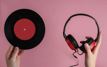 Photo for Female hands hold wired headphones with a vinyl record on pink pastel background. Retro style, DJ. Top view, minimalistic music concept. - Royalty Free Image