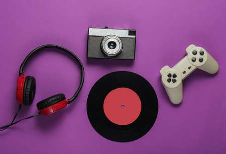 Photo for Pop culture media attributes on purple background. Gamepad, film camera, vinyl record, headphones. 80s. Top view - Royalty Free Image