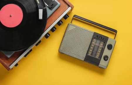 Photo for Retro radio receiver, old-fashioned vinyl player on yellow background. Media 70s. Top view - Royalty Free Image
