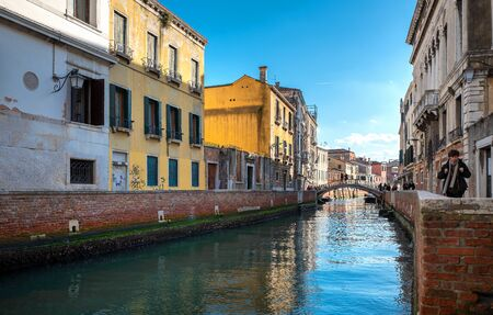 Residential houses, water channels, sights, boats and tourists in Venice, Italy