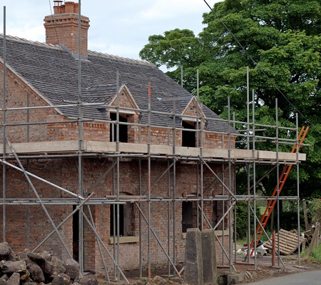 Old country house being renovated with scaffolding in place