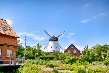 Photo pour Old mill in a green garden in the summertime under a blue sky - image libre de droit