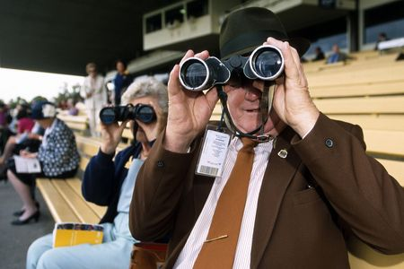 Spectators watch a horse race with binoculars from the stands.