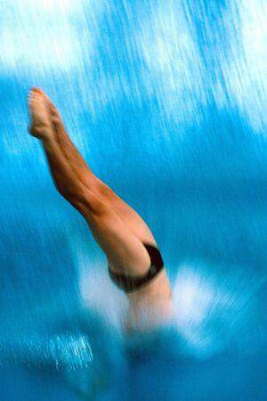 Photo pour A diver is diving into the pool during competition. - image libre de droit