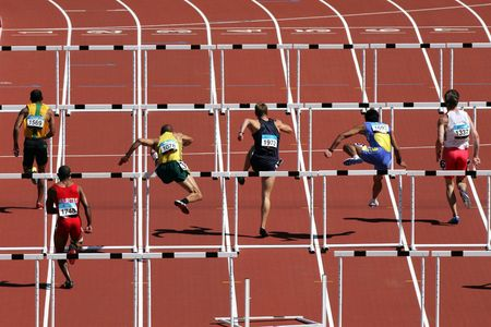 Six lanes of men run over the hurdles in a race.