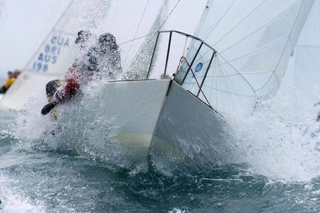 A sailboat tears through the rough seas of the bay.