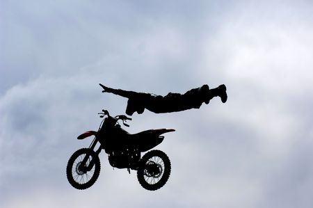 A freestyle motocross rider performs a trick (superman) during a competition.