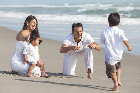 A happy Hispanic family of mother, father and two children, boy sons, playing and having fun in the sand of a sunny beach