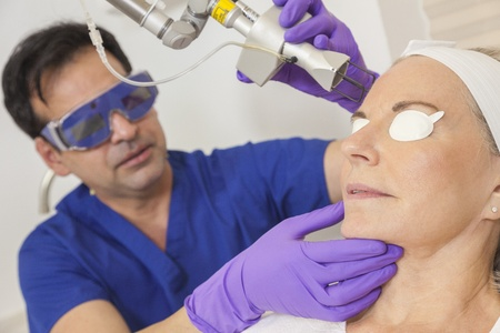 A cosmetic surgeon doctor giving fractional CO2 laser skin treatment to the face of a senior female woman patient