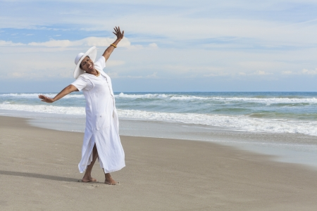 Happy senior African American woman dancing alone on a deserted tropical beach の写真素材