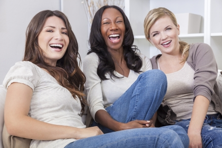 Interracial group of three beautiful young women friends at home sitting together on a sofa smiling and having funの写真素材