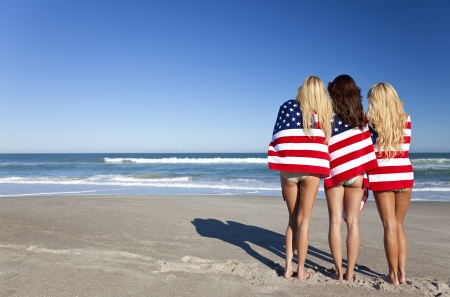Three beautiful young women wearing bikinis and wrapped in American flags on a sunny beach