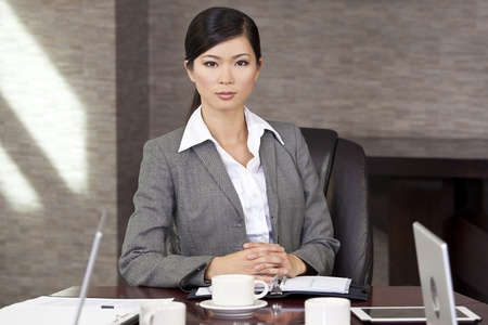 Beautiful Asian Chinese Woman or businesswoman sitting at a boardroom table