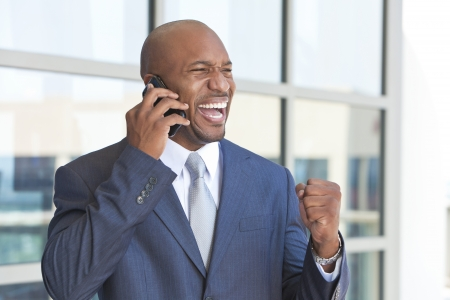 Successful African American businessman or man in a suit in a modern city talking on his cell phone celebrating success
