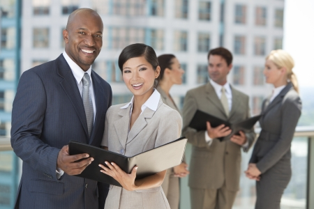 African American businessman and Chinese Asian businesswoman using a black folder with interracial group of business men & women team.