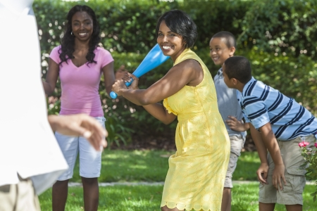 African American family, man, woman, boys, girl, children, mother, father, son playing baseball together outside. The mother is batting.