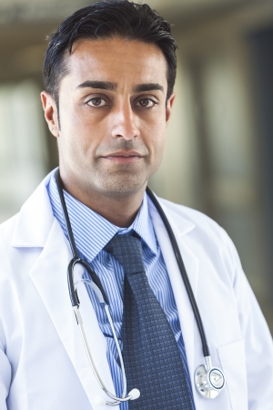 A male Asian Indian man doctor wearing white coat, shirt and tie with stethoscope, pictured in hospital