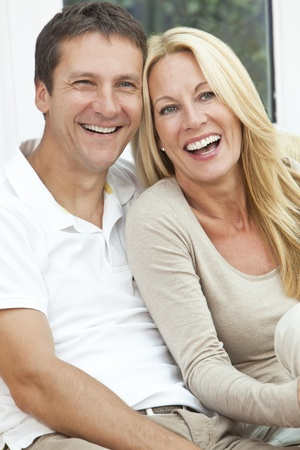 Portrait shot of an attractive, successful and happy middle aged man and woman couple in their forties, sitting together at home on a sofa, smiling and laughing