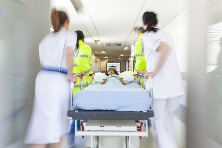 A motion blurred photograph of a young Asian Indian girl child patient on stretcher or gurney being pushed at speed through a hospital corridor by doctors & nurses to an emergency room