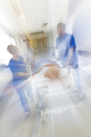 A motion blurred photograph of a senior female patient on stretcher or gurney being pushed at speed through a hospital corridor by doctors & nurses to an emergency room
