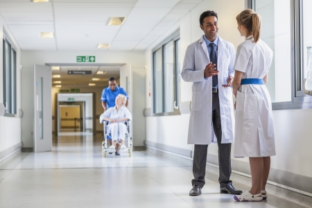 Asian Indian male doctor & female nurse in hospital corridor with a & senior female wheelchair patient and African American nurse in background