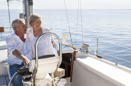 A happy senior couple sailing and sitting at the wheel of a sail boat on a calm blue sea