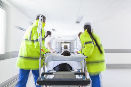 A motion blurred photograph of a patient on stretcher or gurney being pushed at speed through a hospital corridor by doctors & nurses to an accident and emergency room