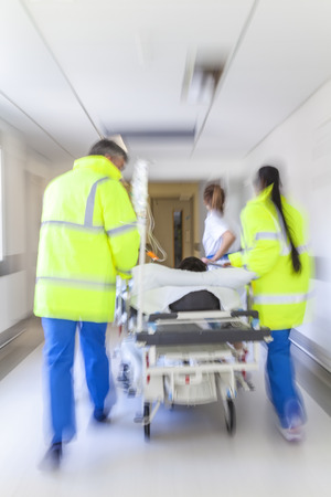 A motion blurred photograph of a patient on stretcher or gurney being pushed at speed through a hospital corridor by doctors & nurses to an emergency room