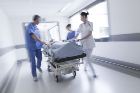 Photo pour A motion blurred photograph of a senior female patient on stretcher or gurney being pushed at speed through a hospital corridor by doctors & nurses to an emergency room - image libre de droit