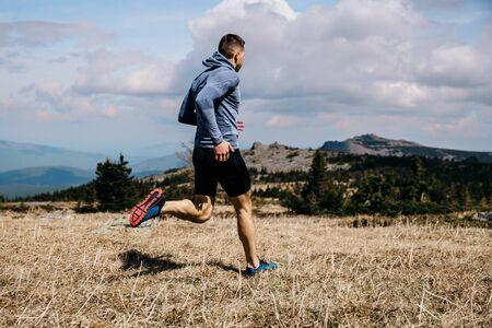 Photo for man runner running mountain marathon trail on yellow grass - Royalty Free Image
