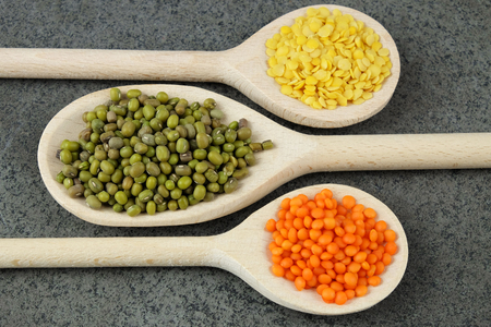 Three wooden spoons with dried green, yellow and red lentils on the dark background.