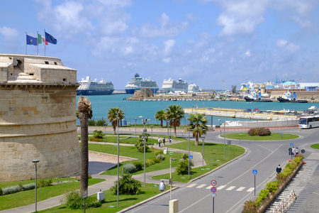 View on the port with three large ships in Civitavecchia, a street and a tower of the Forte Michelangelo - Civitavecchia - Italy.