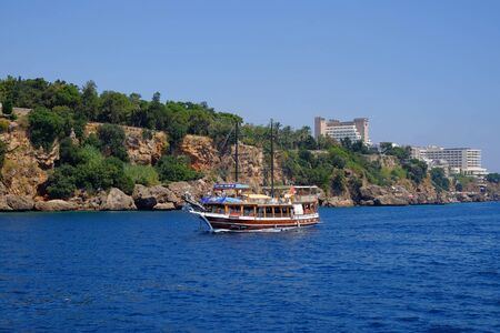 Photo pour ANTALYA, TURKEY - JULY 04 2019: View from the sea on a touristic boat and a coast of Antalya. - image libre de droit