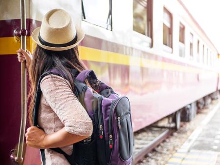 Foto de Closeup a beautiful woman with backpack on the steps of the passenger train. Travel and vacation concept. - Imagen libre de derechos