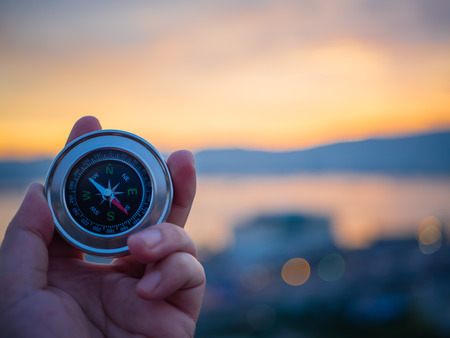 Photo pour Closeup hand holding compass with  mountain and sunset sky background. - image libre de droit