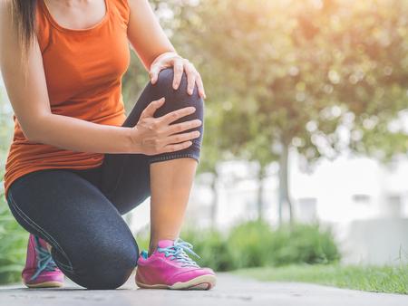 Foto de Runner sport knee injury. Woman in pain while running in the garden. - Imagen libre de derechos